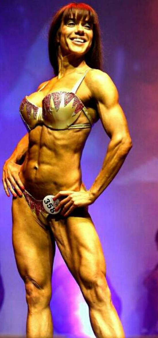 Donna De Lisser posing at the Miami Pro Competition, showing her toned abs and delts