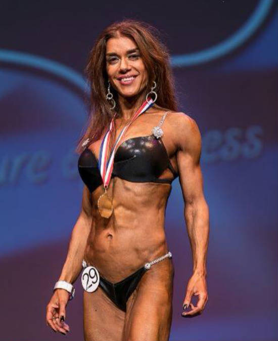 Donna De Lisser standing with her bronze medal at a competition, showing off her toned ans and arms
