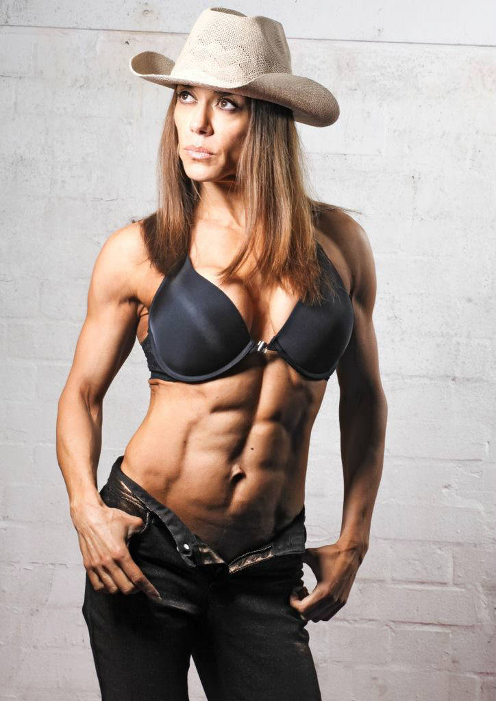 Donna De Lisser wearing a cowboy hat and showing off her ripped abdominals