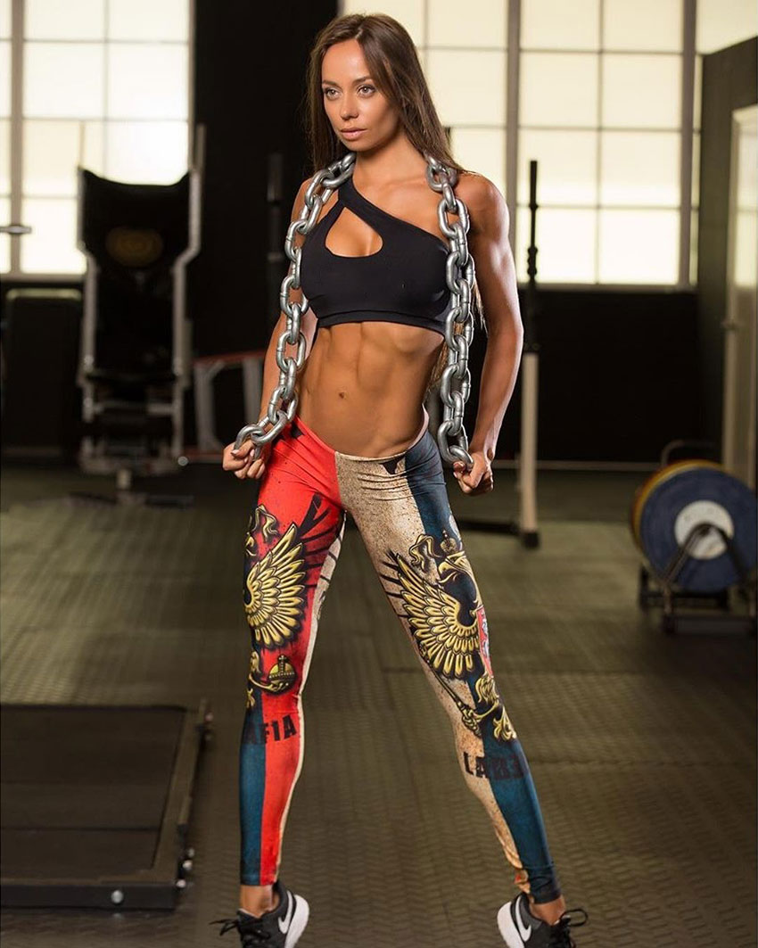 Ekaterina Shokhina posing in the gym holding a weighted chain around her neck, while looking lean and healthy