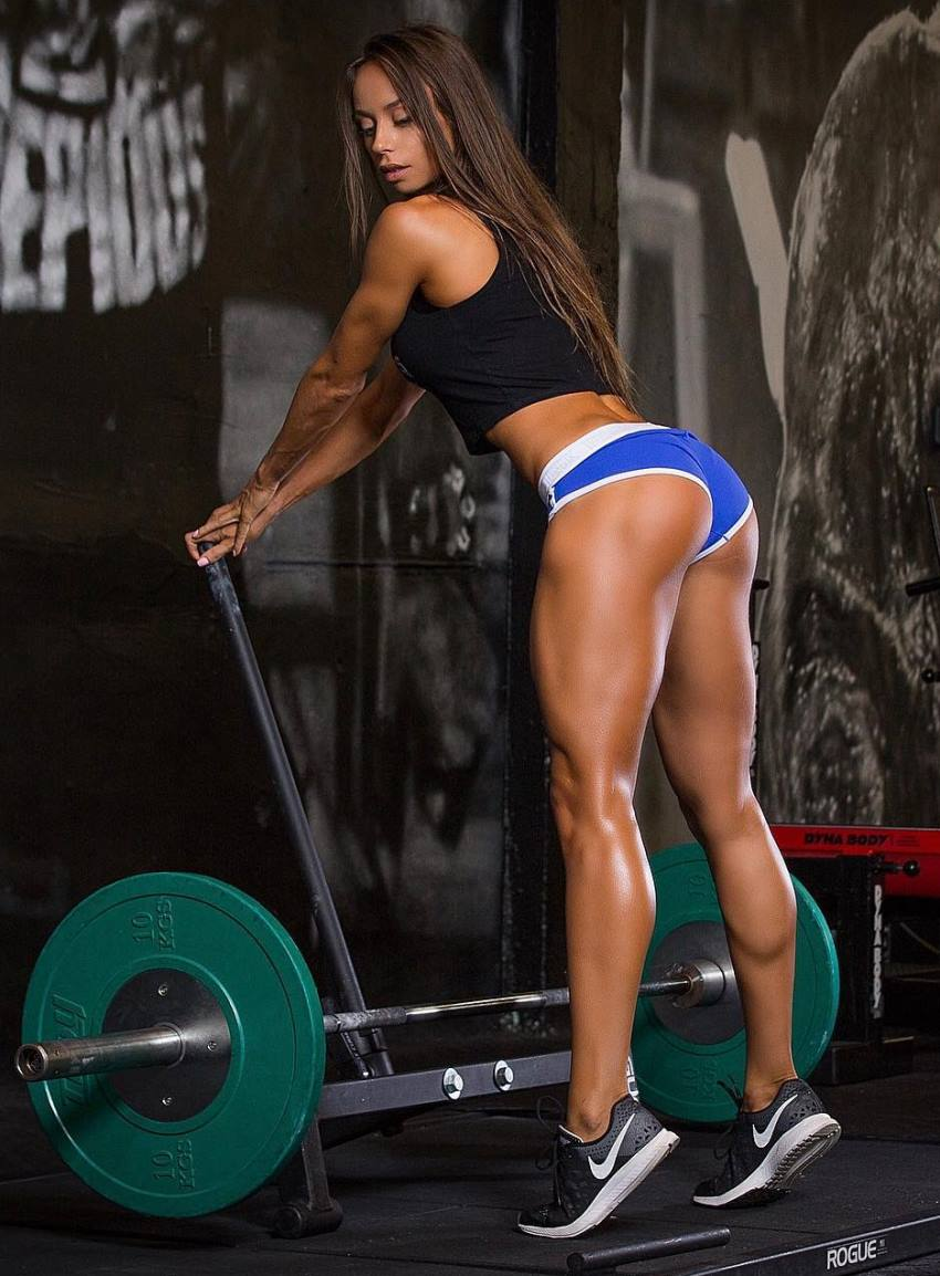 Ekaterina Shokhina standing on her toes besides a olympic bar loaded with green weight plates, showing her calves, legs, and glutes