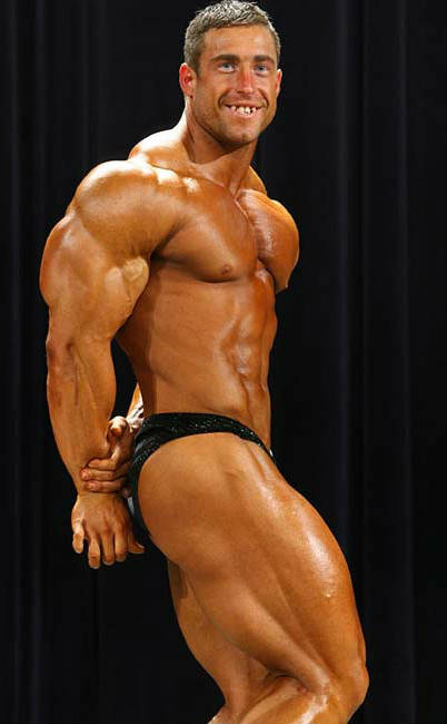 Erik Fankhouser showing his side profile at a competition, displaying his large quads and chest,
