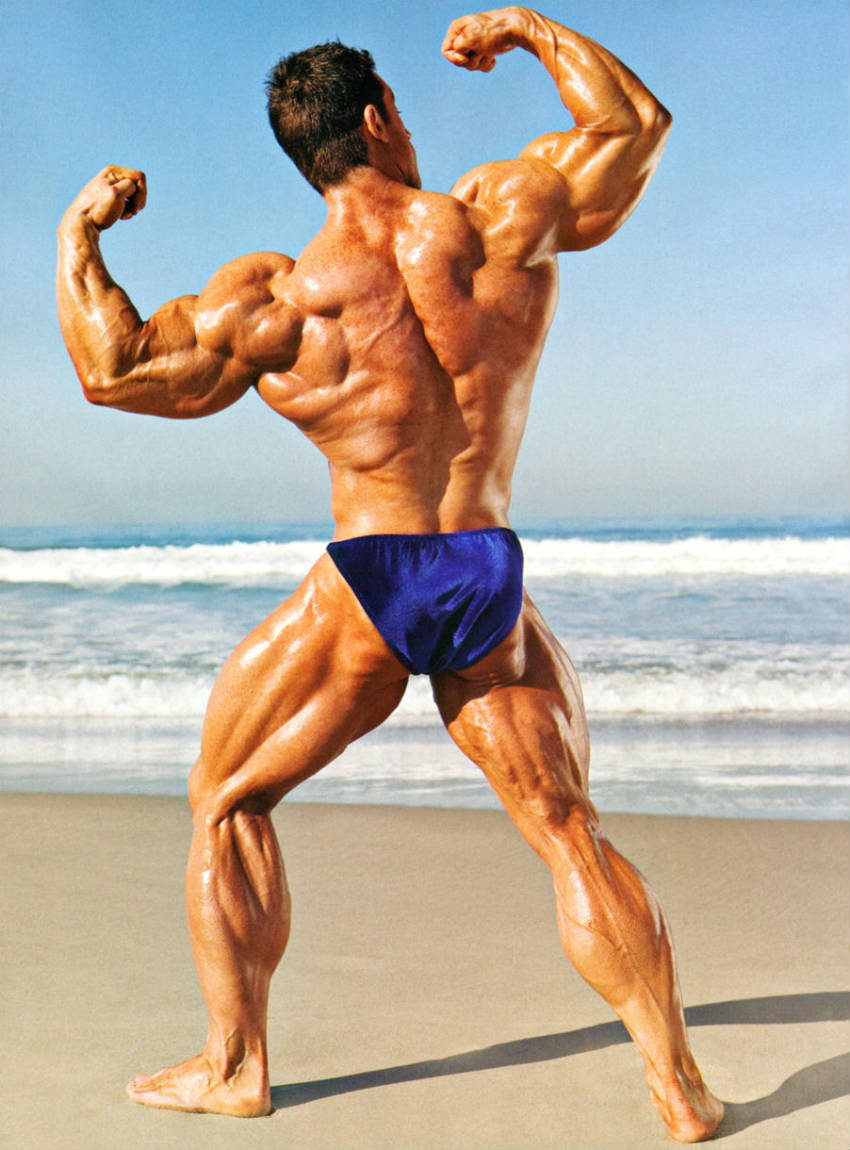Erik Fankhouser standing on the beach showing his back profile to the camera and flexing his arms and back