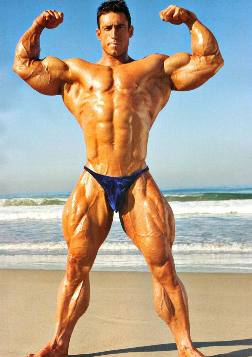 Erik Fankhouser standing on the beach, showing his front profile and tensing his large biceps