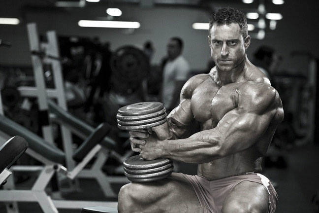 Erik Fankhouser in a black and white photo, sat on the bench in the gym holding a dumbbell and flexing his bicep