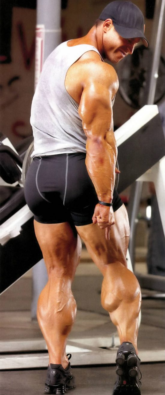 Erik Fankhouser pointing to his large calf following a leg workout