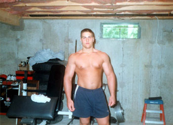 Evan Centopani as a young man showing off his large chest in his basement gym