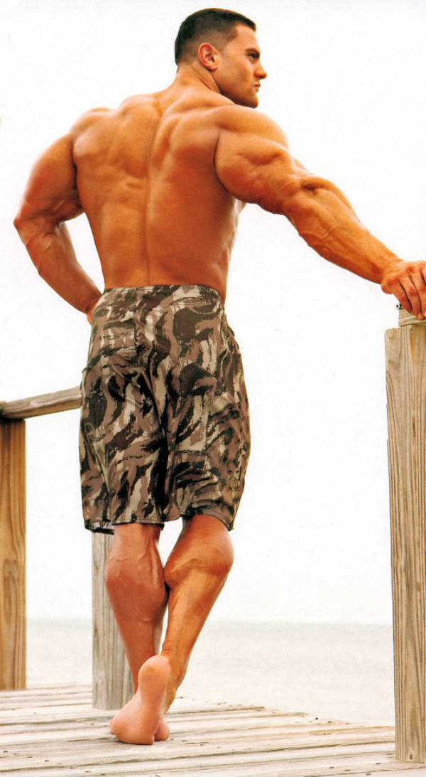 Evan Centopani standing on a pier, showing his large arms, calves and back