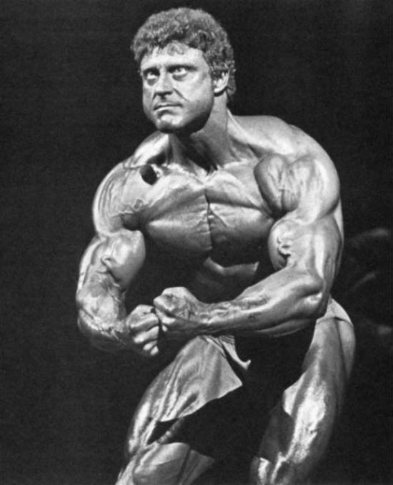 Frank Richards tensing his biceps hard at a competition, showing off his toned and cut body
