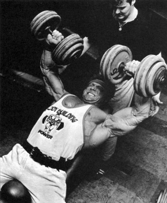 Frank Richards completing a dumbbell bench press with a spotter above him, showing his massive chest and large arms