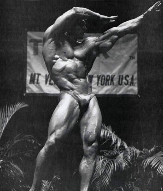 Frank Richards posing in a archers position, showing his big triceps, abs and large quads