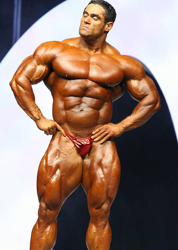 Gustavo Badell posing ta acompetition in a confident stance, showing his large abs, chest and huge quads