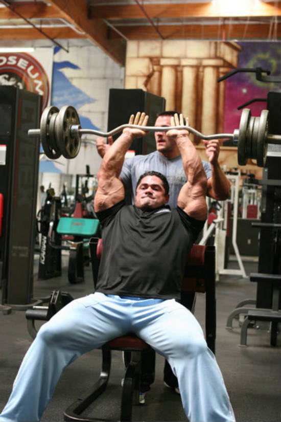 Gustavo Badell completing a barbell tricep exercise in the gym with a spotter