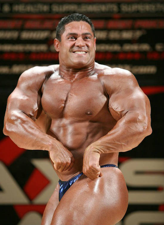 Gustavo Badell posing at a competition, showing off his large arms, bulging chest and toned abs