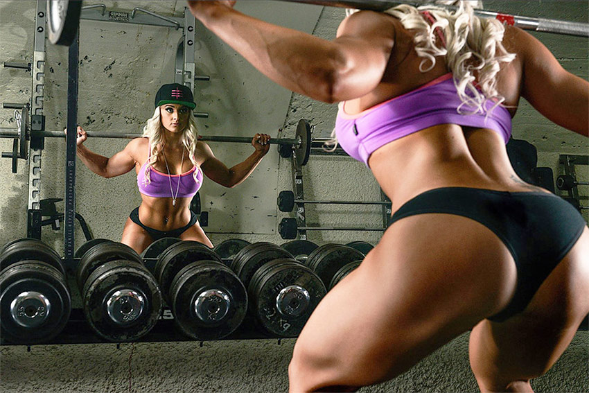 Jade Mead performing squats on the smith machine in a bikini in the gym, wearing a black baseball cap and facing a mirror.