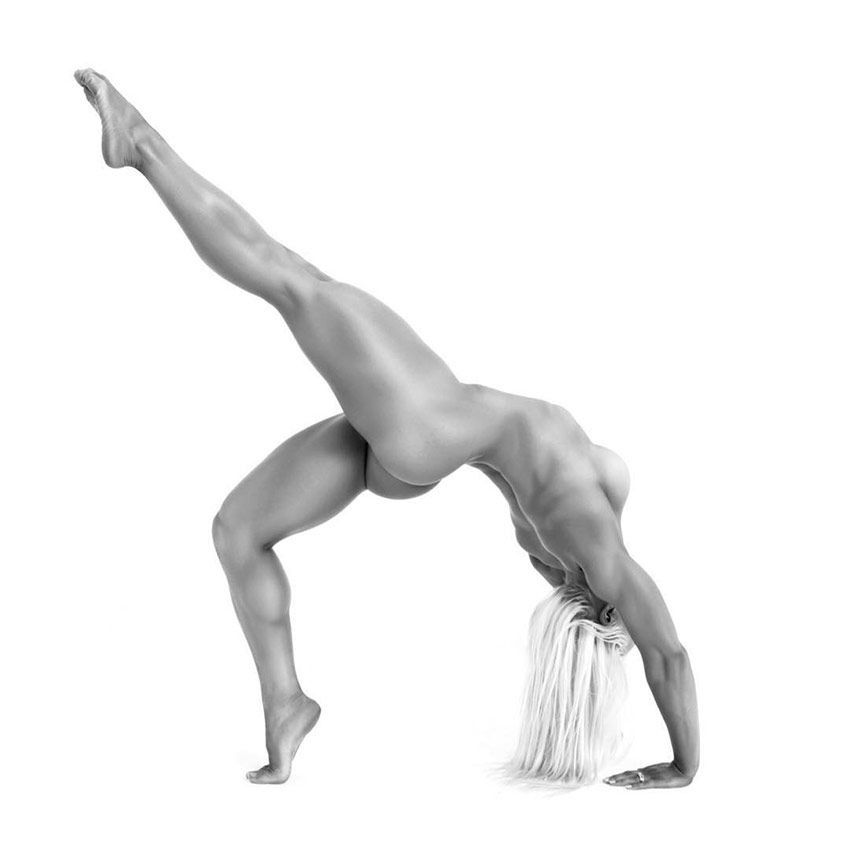 Jade Mead posing naked while performing yoga, displaying the muscular definition on her back, legs, and arms.