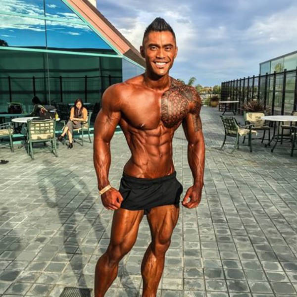 Jake Alvarez showing his full bronzed body before he poses at a competition