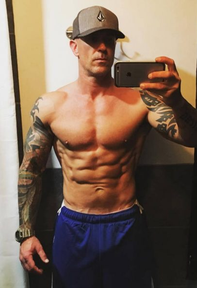 Jason Ferruggia posing with ripped abs, a large chest and vascular arms