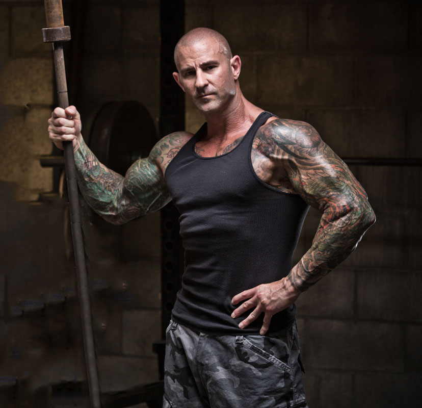 Jim Stoppani posing for the camera holding a barbell looking lean and muscular