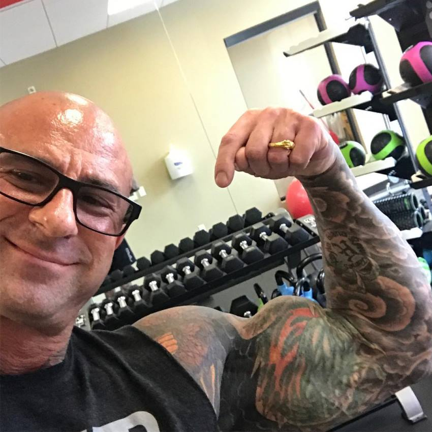 Jim Stoppani wearing glasses, and doing a biceps-flex selfie in a gym, smiling at the camera