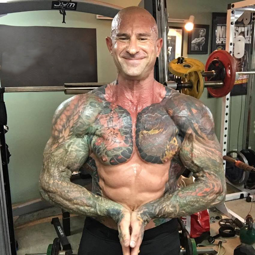 Jim Stoppani in a most muscular pose as he smiles at the camera