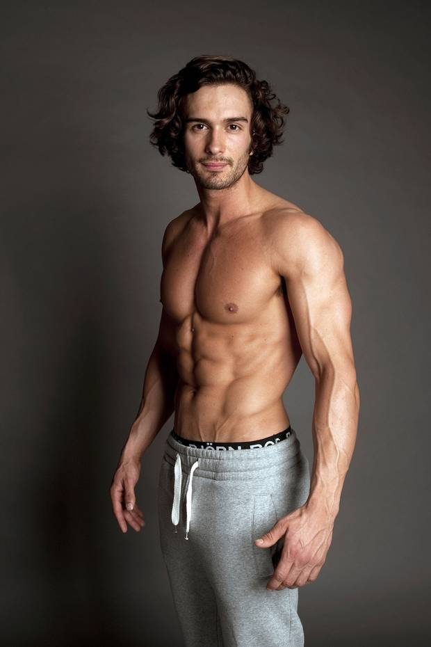Joe Wicks shirtless in grey track pants, displaying his muscular arms, chest, and abs