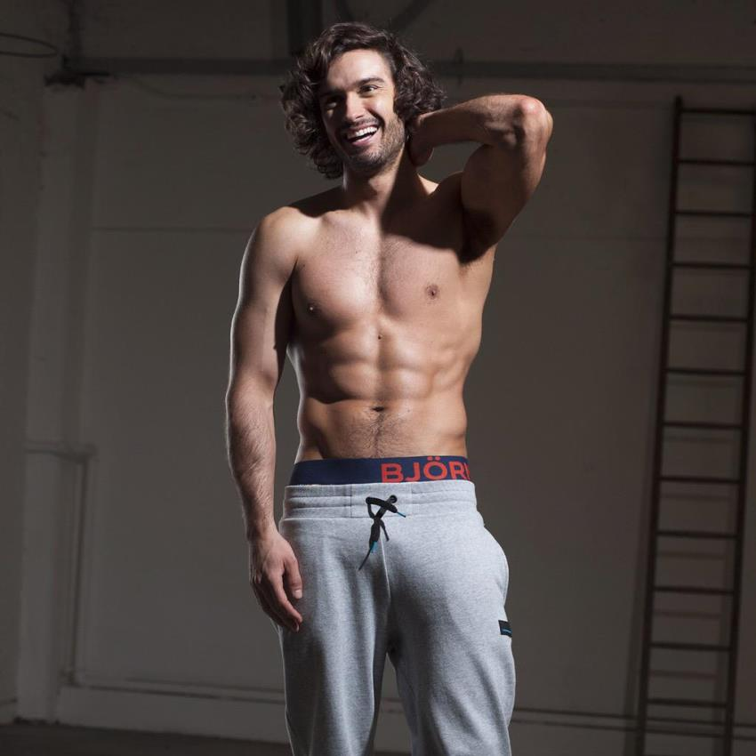 Joe Wicks in grey track pants, smiling and showing his lean upper physique