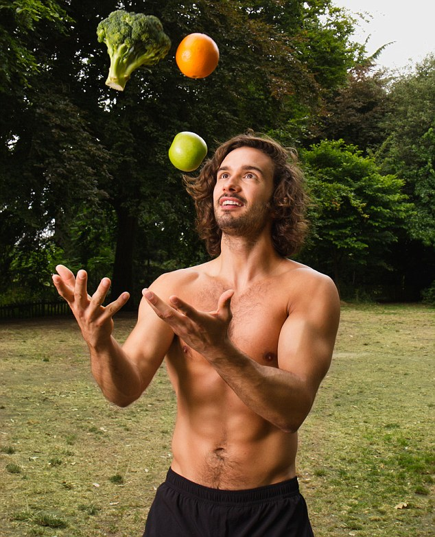 Joe Wicks juggling an orange, apple, and broccoli as he stands in the forest shirtless, displaying his fit upper body