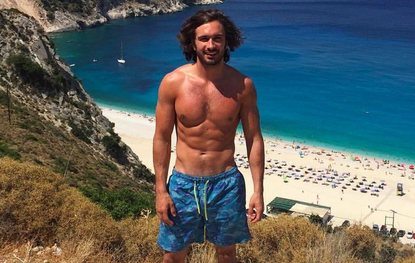 Joe Wicks on a hill which overlooks a beach, flexing his lean abs and chest