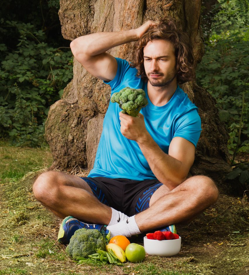 Joe Wicks sitting besides a tree with broccoli in his hand, and other vegetables and fruits on the ground, having one of his hands in the air, and thinking about something