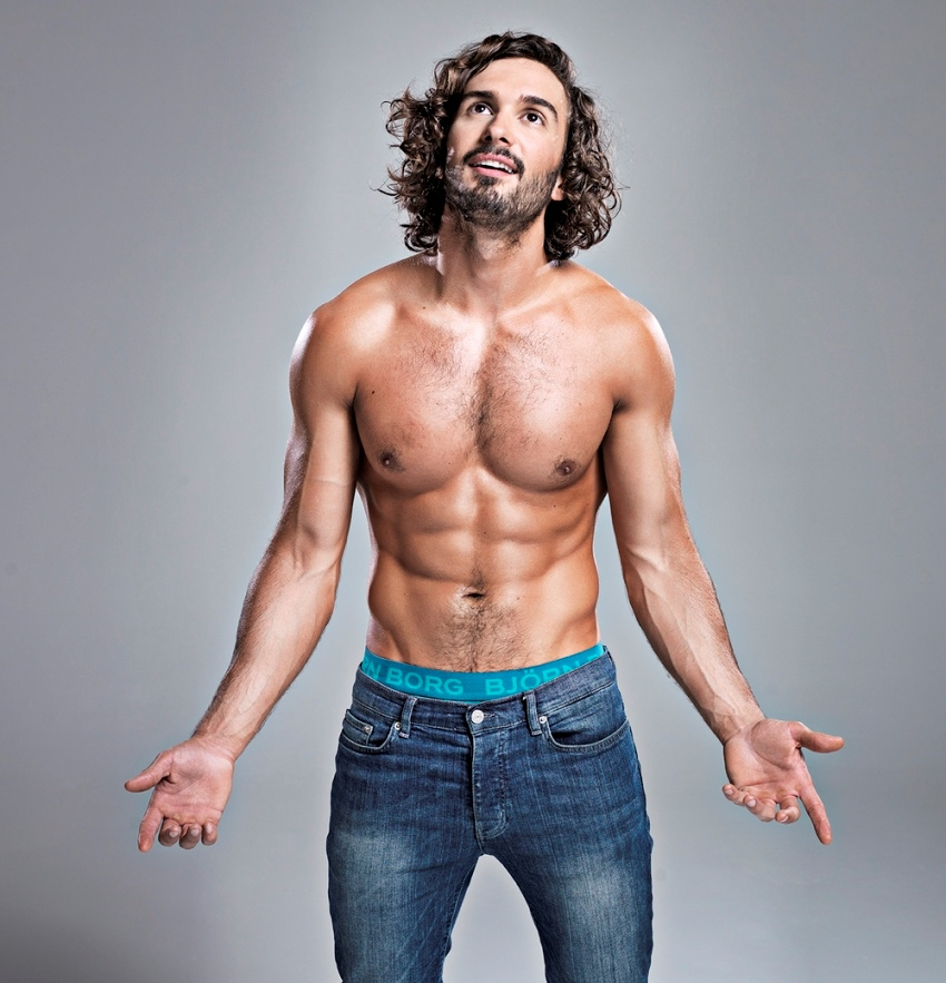 Joe Wicks posing shirtless for a photoshoot, showing his oiled up, fit body