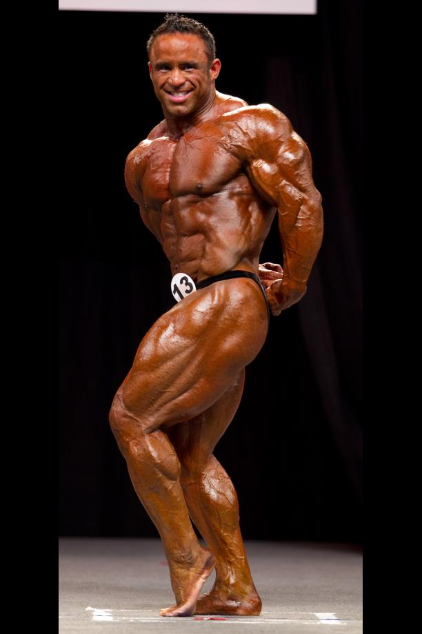 Jose Raymond showing his side profile at a competition, displaying his large quads and arms