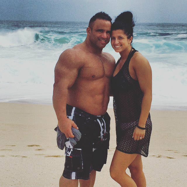 Jose Raymond standing on the beach with his wife, showing off his upper body in the off-season