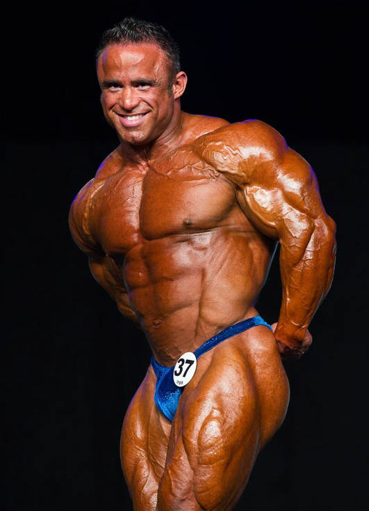 Jose Raymond tensing his bulging triceps and deltoids at a competition