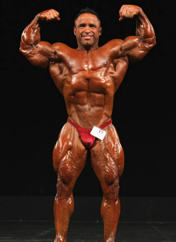Jose Raymond tensing his large biceps above his head at a competition