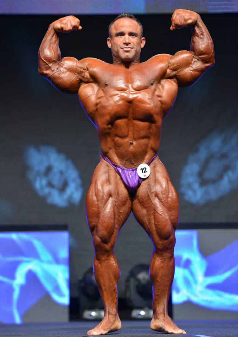 Jose Raymond showing his large abdominal and arm muscles at a competition