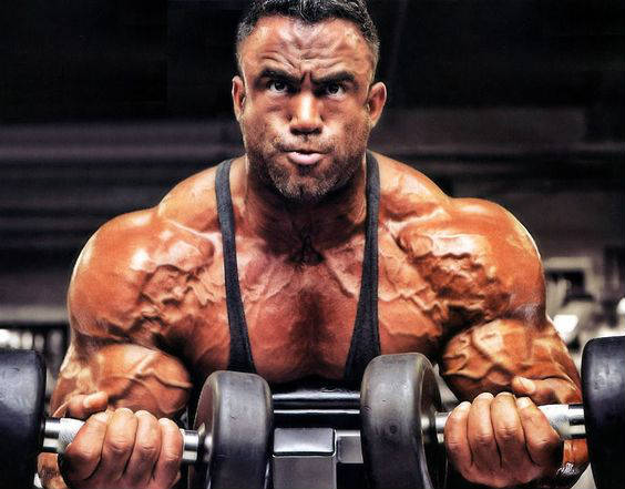 Jose Raymond completing a dumbbell curl with two weights, displaying his well-built shoulders and arms