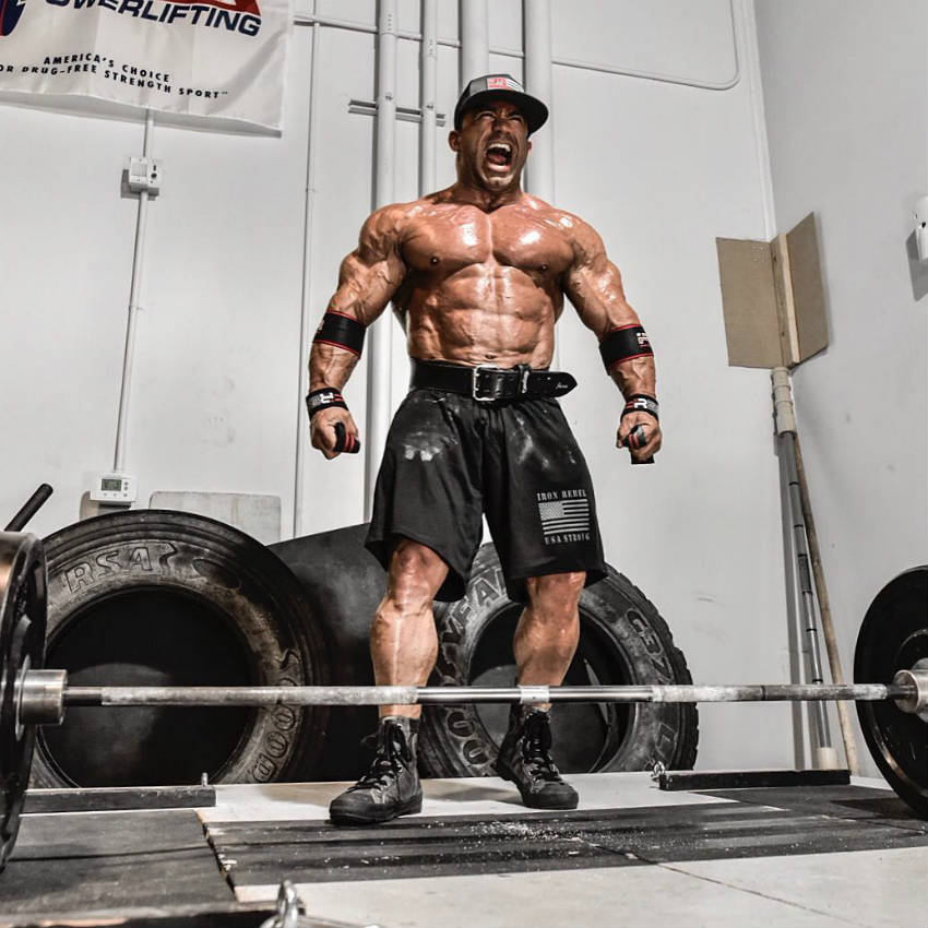 Jose Raymond standing in front of a barbell screaming and showing his well-built upper body