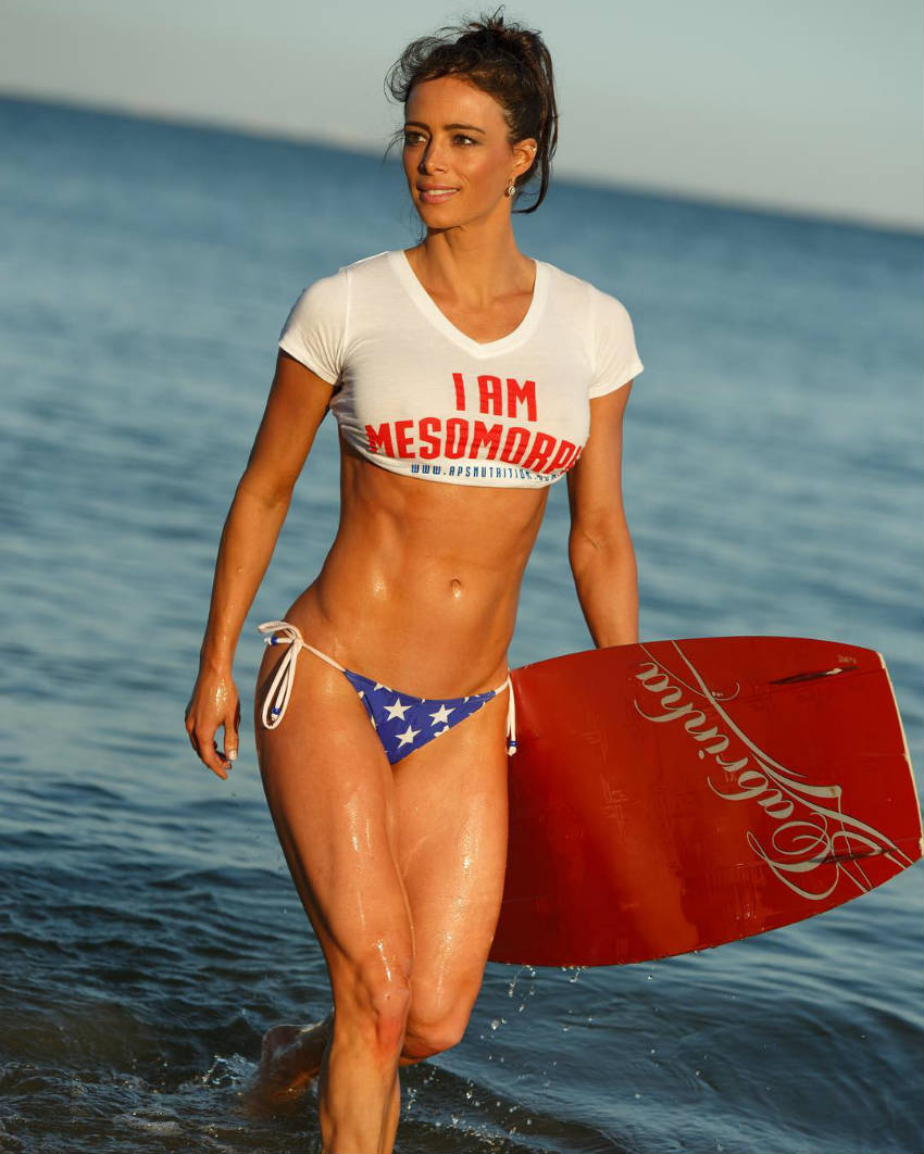 Juliana Daniell walking out of the water with a bodyboard, showing her toned abs and quads
