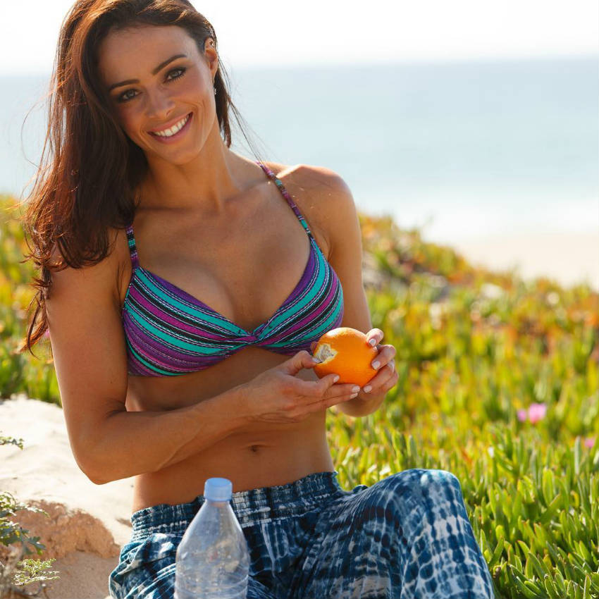 Juliana Daniell eating an orange and showing off her toned abs and arms