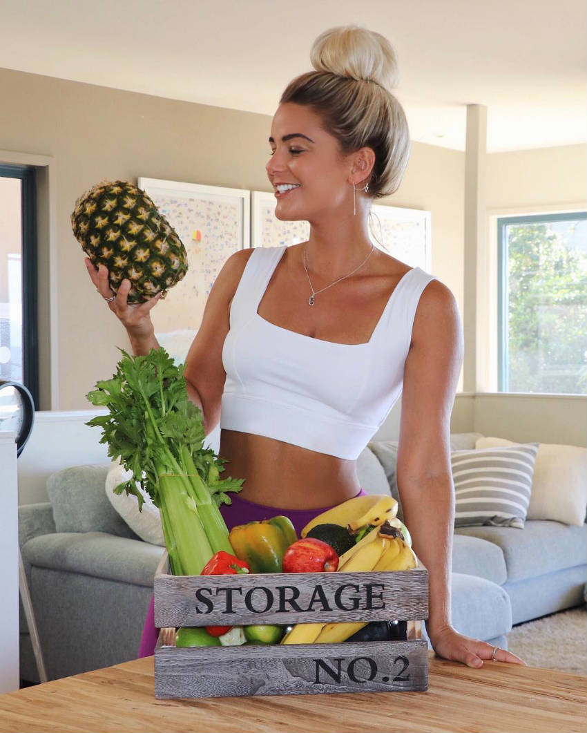 Karina Irby holding a pineapple, showing off her toned arms and abs