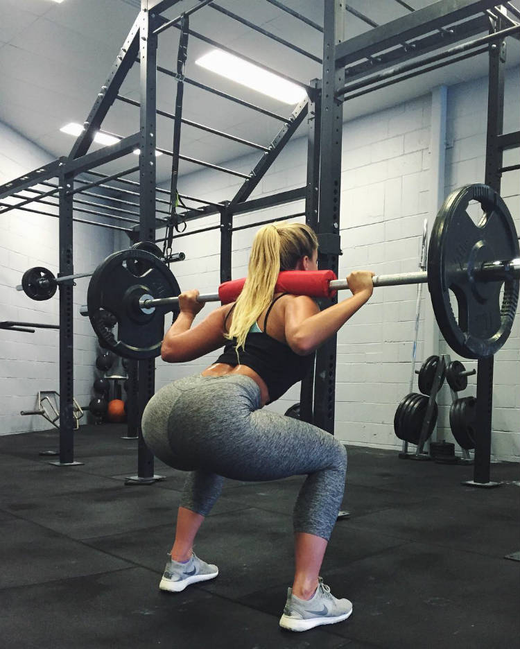 Karina Irby completing a barbaell squat, showing her toned glutes and legs