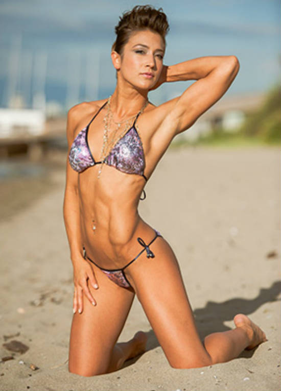 Kimberly Hoogendoorn kneeling on the beach, showing off her ripped abs and obliques