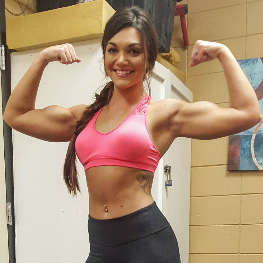 Kristie Crider doing a front double biceps pose in a sportswear, as she smiles at the camera