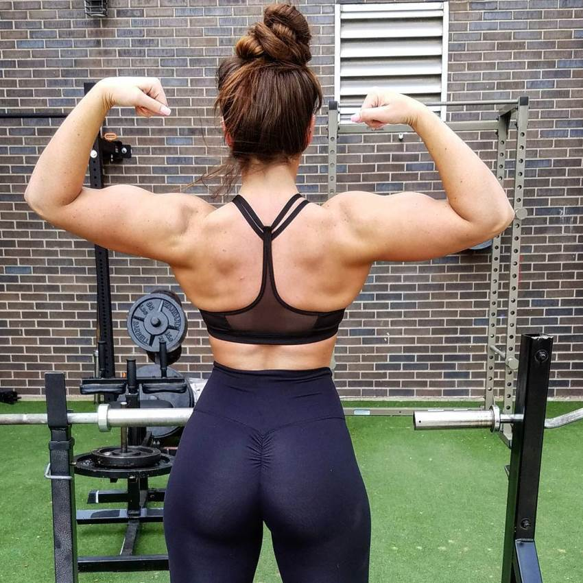 Kristie Crider doing a back double biceps pose in black sportsbra and yoga pants, showing off her muscular and aesthetic looks