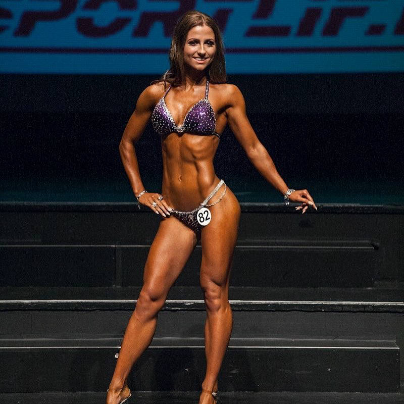 Kristin Gudlaugsdottir posing at a competition, showing her toned abs, legs and arms
