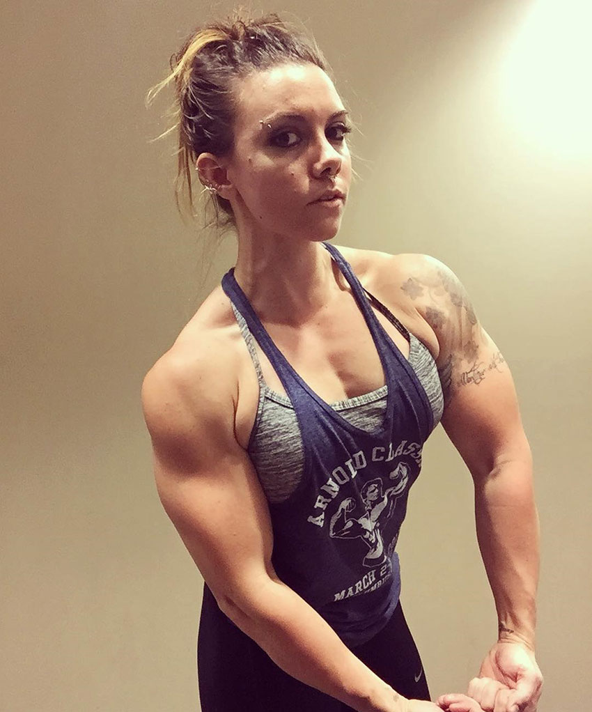Kristina Moser flexing her chest and arms while wearing a gym tank top under a light, highlighting her huge muscles