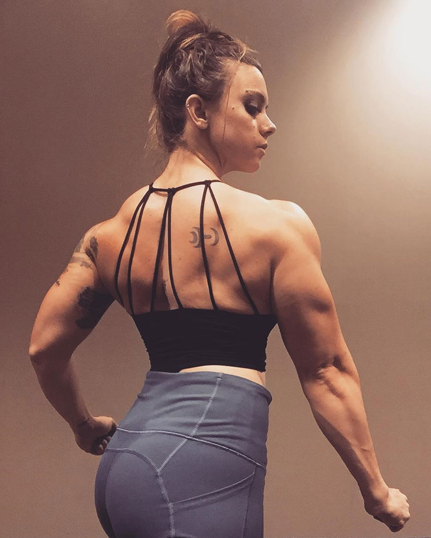 Kristina Moser is standing under a light wearing a stringed backed crop top showing her huge back, and arm muscles