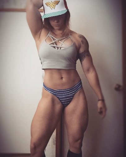 Kristina Moser wearing her underwear and a tight top looking lean, muscular, and happy
