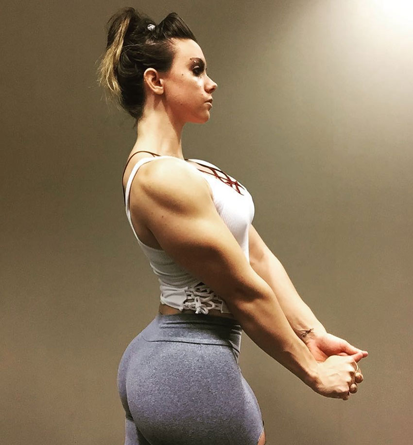 Kristina Moser standing under a light while holding her hands together flexing her triceps and glutes at the same time in a classic bodybuilders pose looking big and muscular